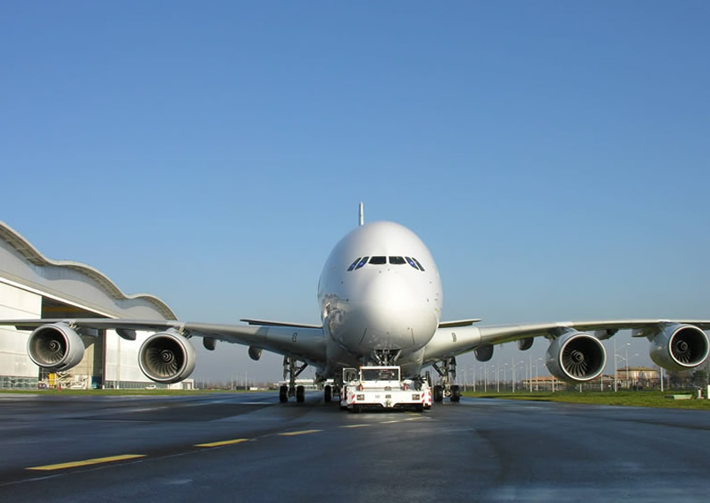 Airbus A380 being towed by tug on taxiway